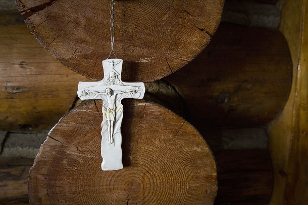 Crucifix dangling from long rosary is seen against logs in retreat lodge at Shrine of St. Therese in Juneau, Alaska