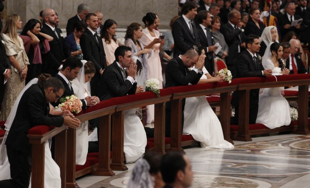 Newly married couples kneel as Pope Francis celebrates marriage rite for 20 couples during Mass at Vatican