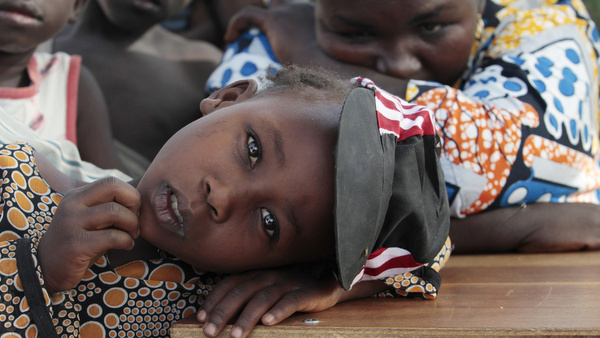 Girl displaced as a result of Boko Haram attack in Nigeria rests her head on desk at camp for displaced people