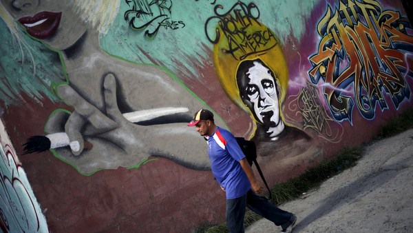 Man walks next to wall with graffiti bearing image of Archbishop Oscar Romero in San Salvador