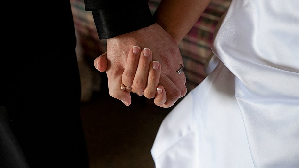 A groom and bride hold hands on their wedding day. Catholic marriages in the United States are at their lowest point since 1965. (CNS file photo/Jon L. Hendricks) See CATHOLIC-MARRIAGE March 19, 2015.