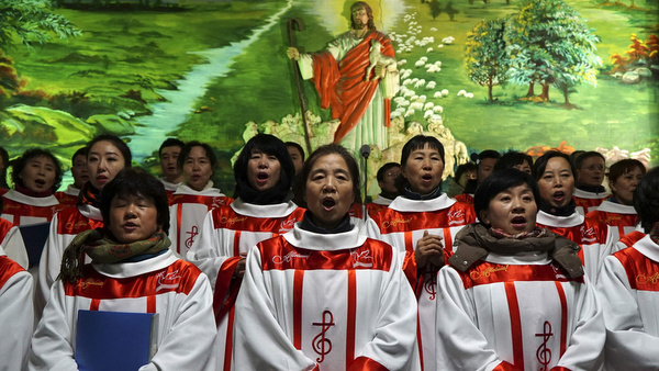 Choir members sing carols in front of a figure of Christ during Christmas Eve Mass at a Catholic church in Shenyang, China. (CNS photo/Sheng Li, Reuters)