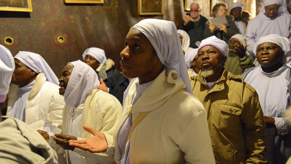 Nigerian Christians pray in the grotto of the Church of Nativity on Christmas Eve in Bethlehem, West Bank. (CNS photo/Debbie Hill) See CHRISTMAS-PALESTINIANS Dec. 26, 2014.