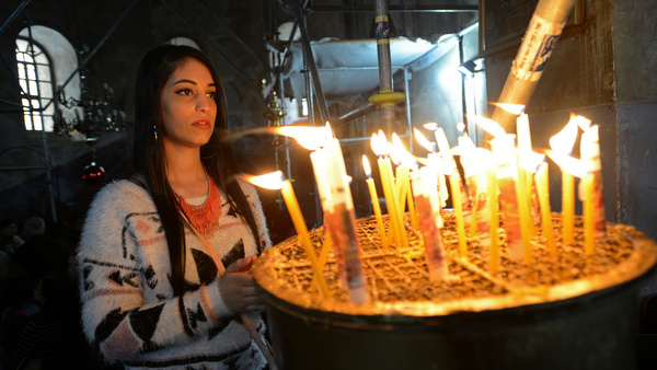 A Palestinian Christian prays in the Church of Nativity on Christmas Eve in Bethlehem, West Bank. (CNS photo/Debbie Hill) See CHRISTMAS-PALESTINIANS Dec. 26, 2014.