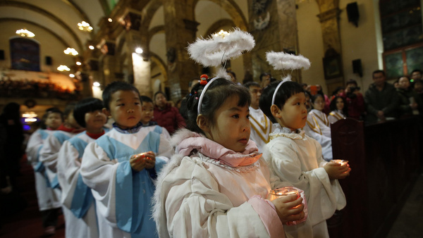 Children dressed as angels carry candles as they attend Christmas Mass at a Catholic church in Beijing Dec. 24. (CNS photo/Kim Kyung-Hoon, Reuters)