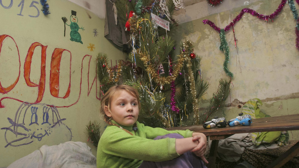 A girl sits near Christmas decorations in a basement used as a bomb shelter in Donetsk, Ukraine, Dec. 30. (CNS photo/Igor Tkachenko, Reuters)
