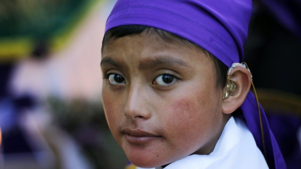 Child dressed as penitent takes part in Way of Cross in Guatemala City