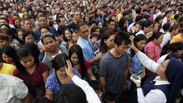 Nun and a lay minister mark crosses on forehead of people during Ash Wednesday Mass outside church in Manila