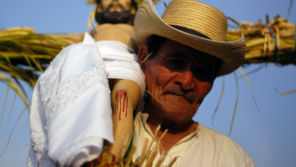 A man carries a statue of Christ on the cross while participating in a Holy Thursday procession in Izalco, El Salvador, April 5. Catholics throughout Latin America celebrate Holy Week with processions and religious festivals. (CNS photo/Ulises Rodriguez, Reuters) (April 6, 2012)