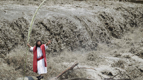 Actor portraying Christ performs during  Holy Week celebrations along river in Peru