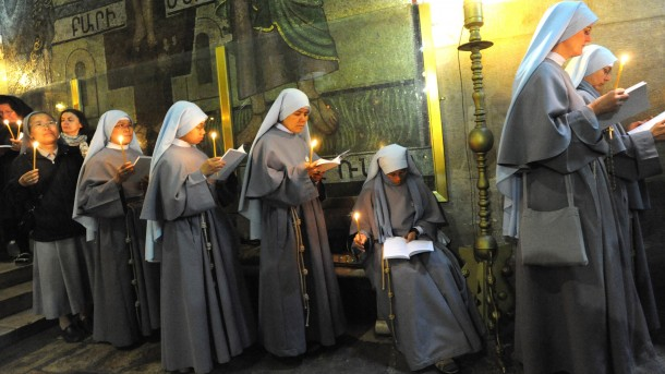 NUNS HOLD CANDLES DURING EASTER MASS AT CHURCH OF THE HOLY SEPULCHER IN JERUSALEM