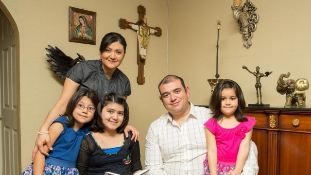 Family of five at home with religious objects in background