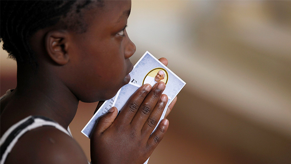 Little girl holds Pope Francis prayer card during Mass.