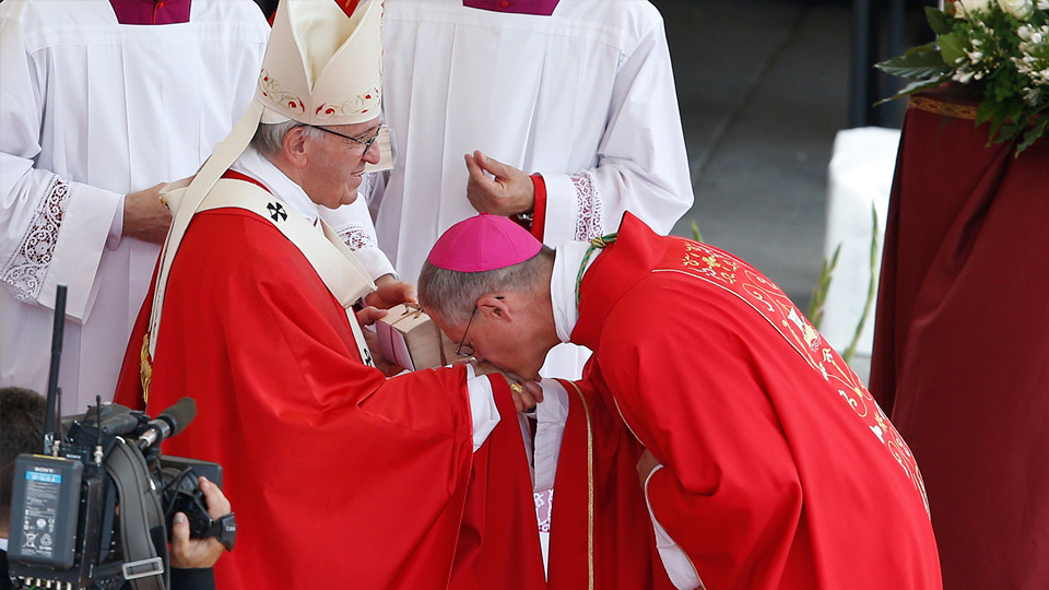 Archbishop Paul D. Etienne of Anchorage, Alaska, kisses Pope Francis' hand as he receives his pallium at the conclusion of a Mass marking the feast of Sts. Peter and Paul in St. Peter's Square at the Vatican June 29. New archbishops from around the world received their palliums from the pope. The actual imposition of the pallium will take place in the archbishop's archdiocese.