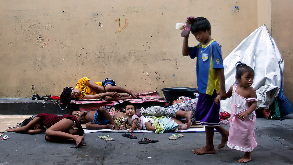 """Homeless Filipinos rest in late April on a street in Manila. World Day of the Poor, to be celebrated Nov. 19 this year, will focus on the apostle John's call to love """"not with words, but with deeds."""""""