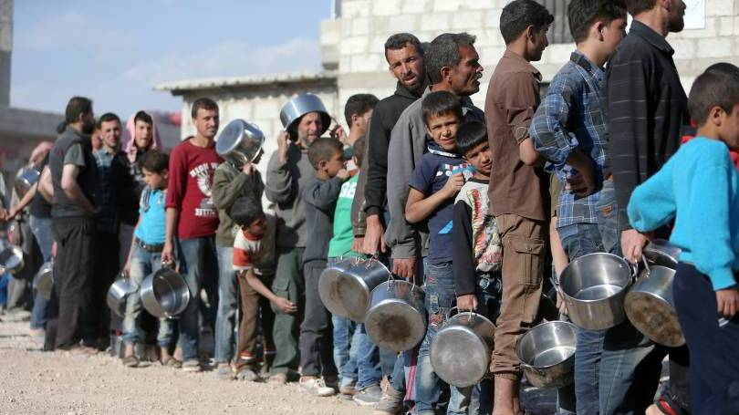Internally displaced Syrians wait in line for food April 15 at a camp outside Damascus.