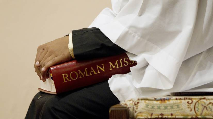 altar server holds a Roman missal