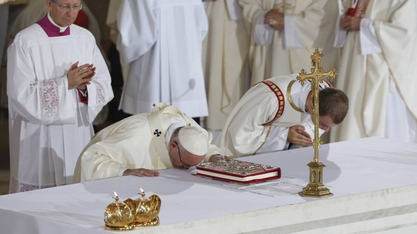 Pope Francis kisses the altar at the beginning of Mass