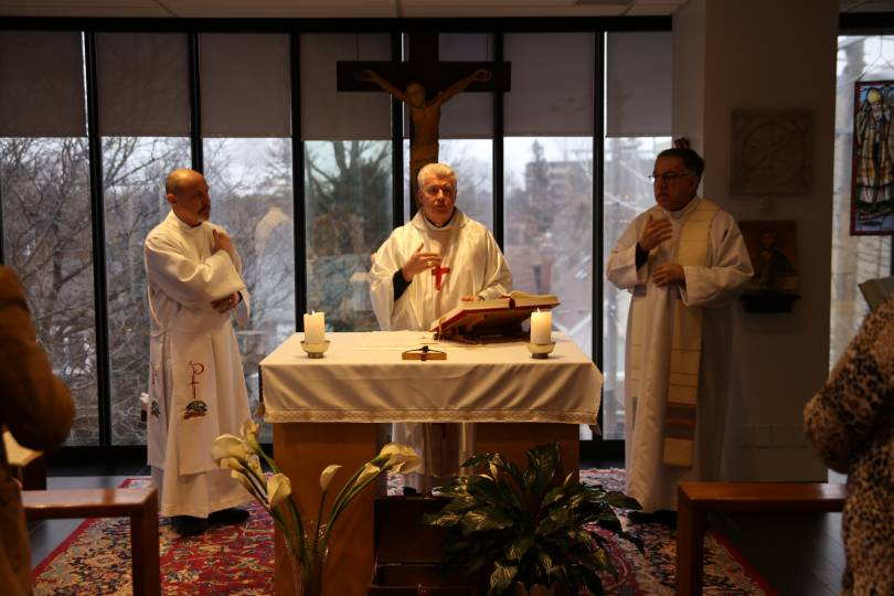 Priests and deacon make the sign of the cross at the beginning of Mass