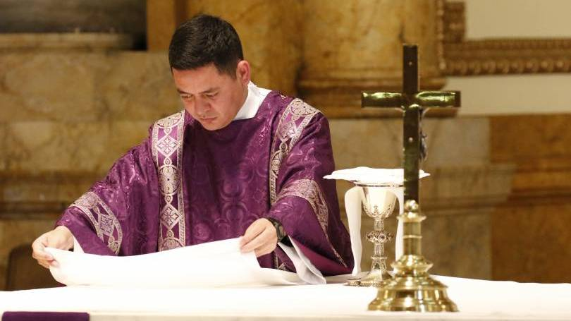 A deacon prepares the altar during Mass