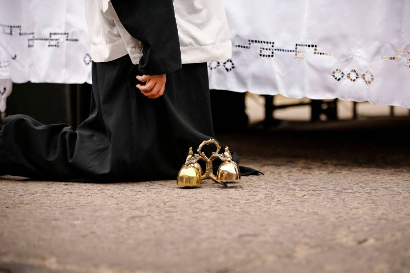 An altar servers kneels by the altar with bells nearby