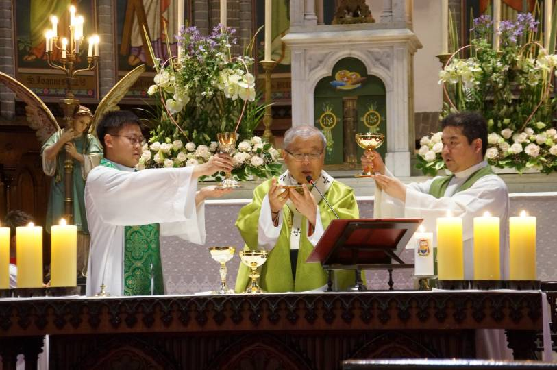 Three priests raise the paten and chalices during the doxology