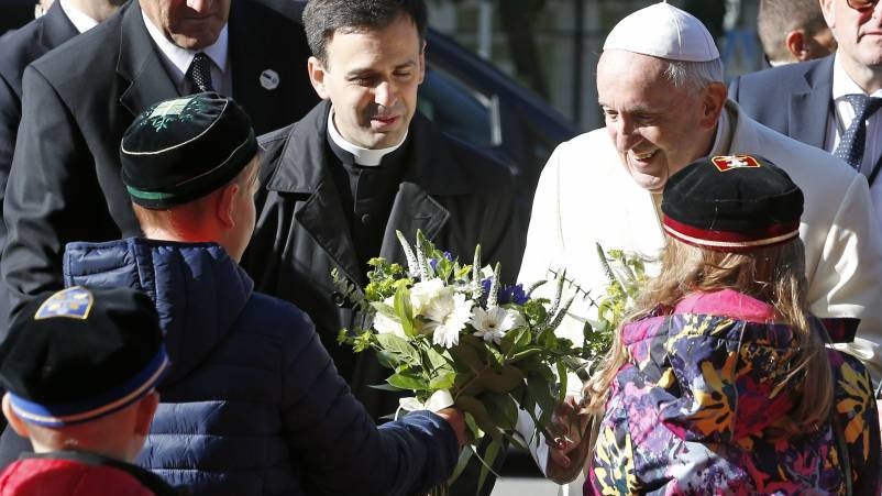 Pope Francis accepts flowers from children as he arrives at an ecumenical encounter with young people at the Kaarli Lutheran Church in Tallinn, Estonia