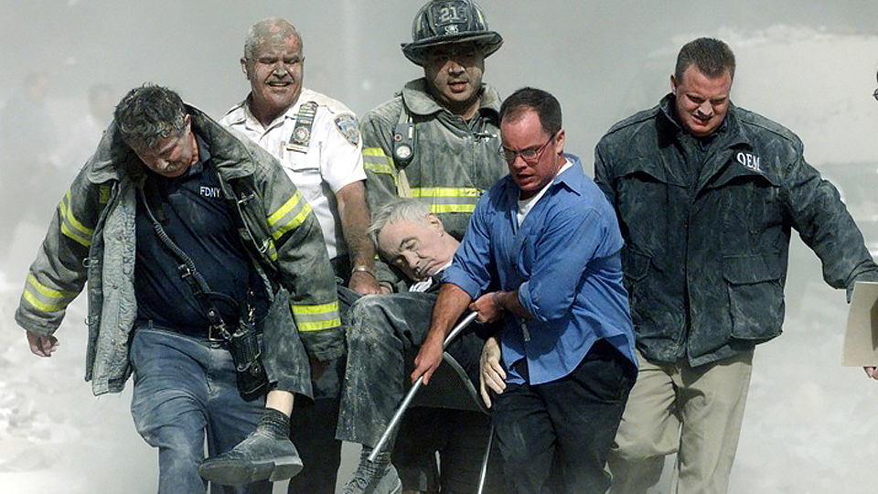 Firefighters carry the dead body of NY Fire Department chaplain, Fr. Mychal Judge, OFM, from the debris of the World Trade Center in New York City. Fr. Judge was one of the first people to die after the Twin Towers were hit on September 11, 2001.