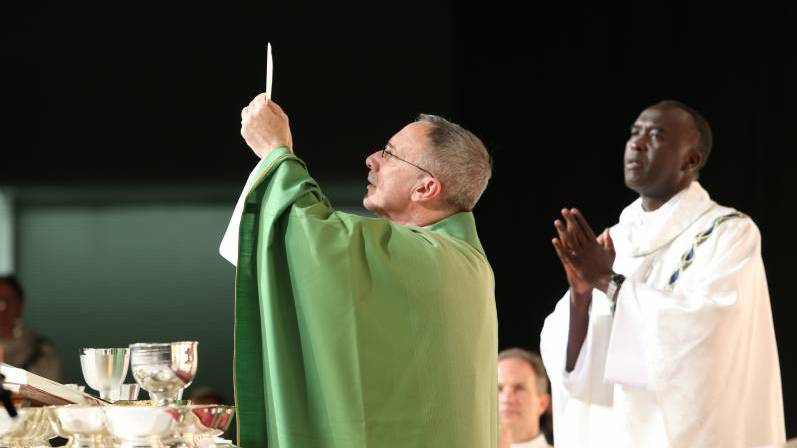 A priest elevates the Eucharist during the consecration