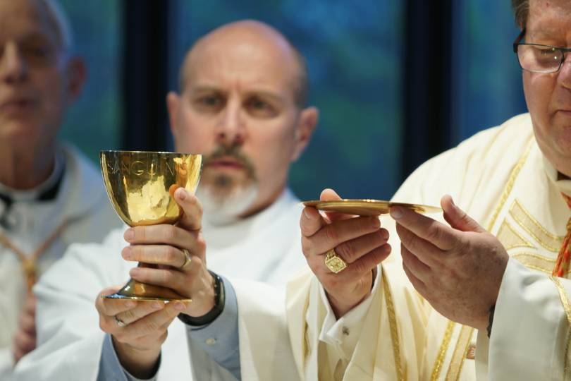 A priest and a deacon elevate the Eucharist and the Chalice during the doxology