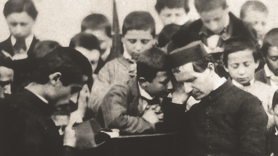 Saint John Bosco hears confession from a group of children. Archival photo courtesy of Salesians of Don Bosco in the United States (USA West Province).