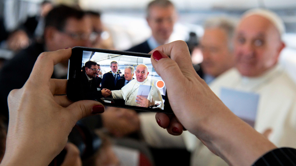 Pope Francis interacts with journalists during his flight to Panama. (CNS photo/Vatican Media)
