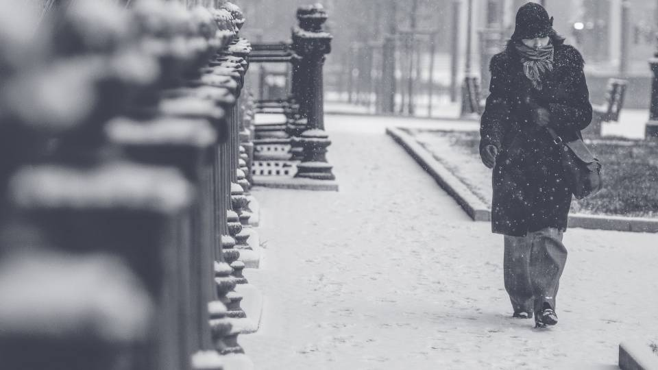 Woman wrapped in coat, scarf, and hat walks on a snowy sidewalk