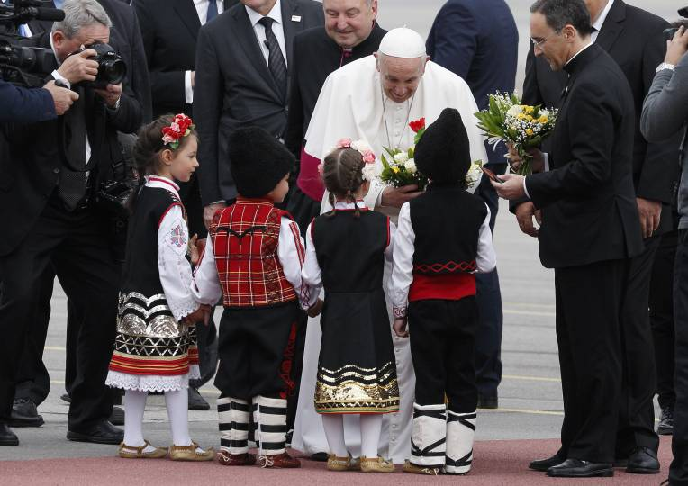 Pope Francis greets children in traditional dress as he arrives at the airport in Sofia, Bulgaria, May 5, 2019. (CNS photo/Paul Haring)