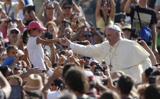Pope Francis greets girl as he arrives to lead general audience