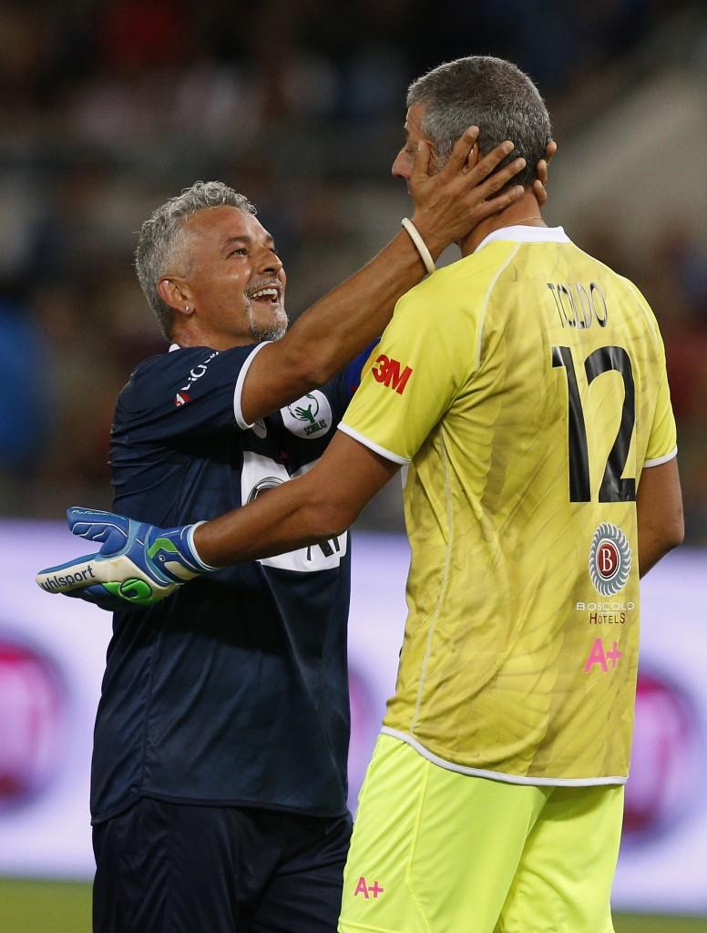 Former Italian soccer player Roberto Baggio embraces former Italian goalie Francesco Toldo during 'Interreligious Match for Peace'