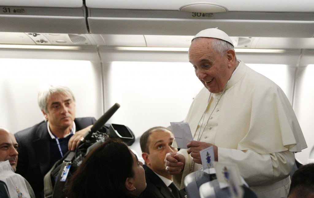 Pope Francis accepts envelope while greeting media aboard flight to Colombo, Sri Lanka