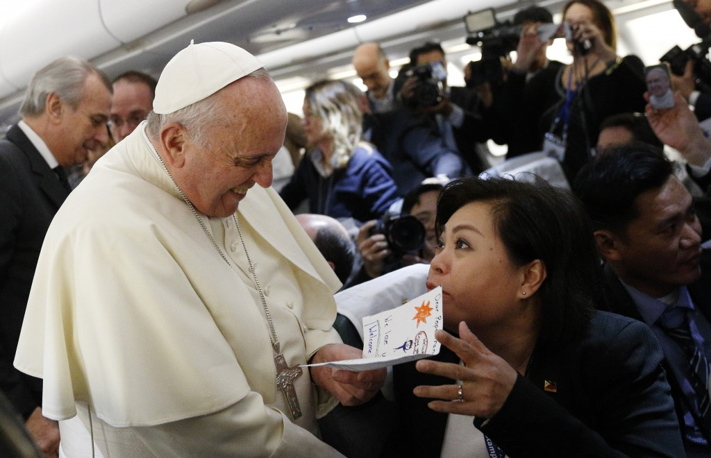 Pope Francis accepts card from Filipino reporter aboard flight to Colombo, Sri Lanka