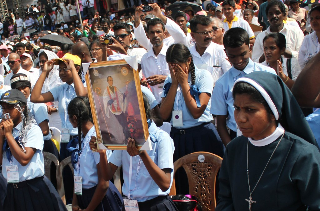 Young woman holds image of St. Joseph Vaz during canonization in Sri Lanka