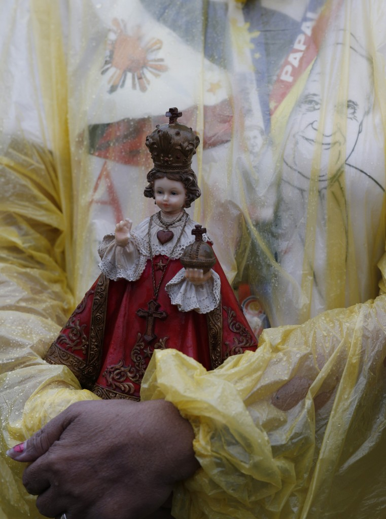 Woman holds statue of statue of Santo Nino as Pope Francis celebrates Mass at Rizal Park in Manila, Philippines