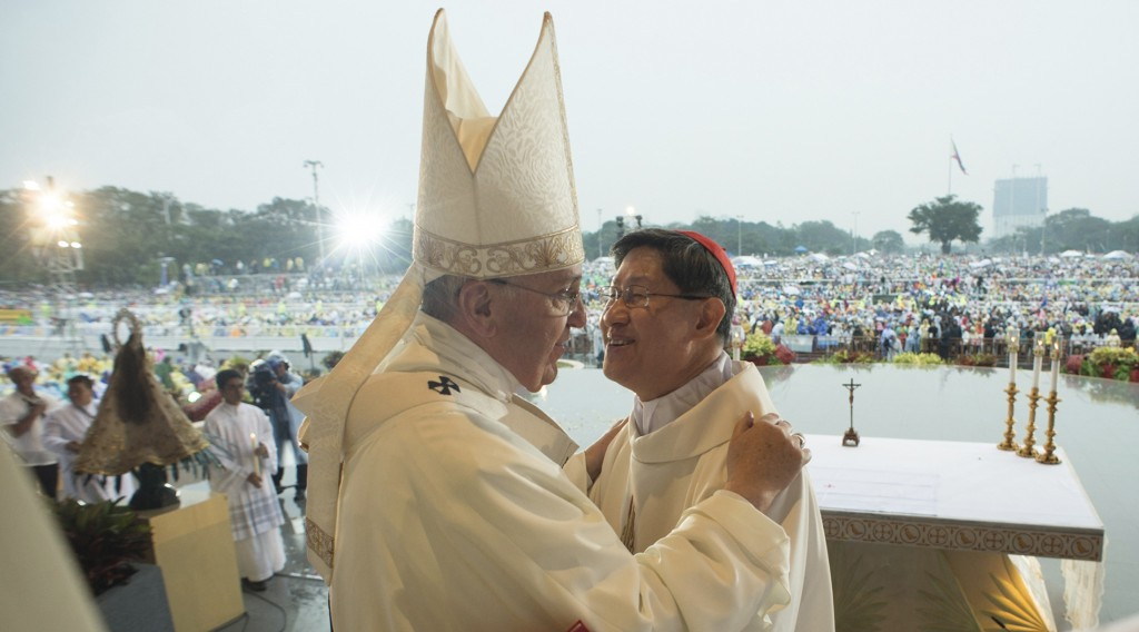 Pope Francis embraces Cardinal Tagle as he celebrates a Mass at Rizal Park in Manila