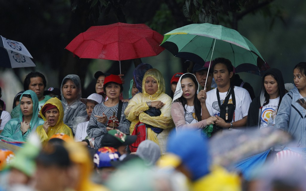 People wait to see Pope Francis along his motorcade route after Mass in Rizal Park in Manila