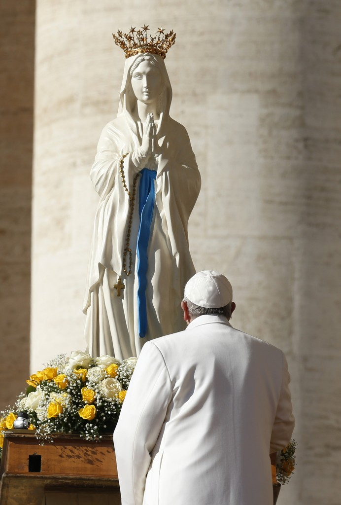 Pope Francis prays in front of statue of Mary as he begins general audience in St. Peter's Square